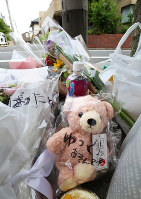 Flowers, toys and drinks are seen placed in front of the apartment where Yua Funato, who died of suspected neglect in March this year, lived with her parents, on June 8, 2018, in Tokyo's Meguro Ward. The message written on the bag containing the teddy bear reads,