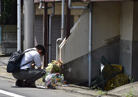 A man prays in front of a spontaneous memorial to Yua Funato, who died of suspected neglect in March this year, in front of the apartment where she lived with her parents, on June 9, 2018, in Tokyo's Meguro Ward. (Mainichi)