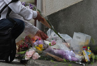 A visitor adds flowers to a spontaneous memorial to Yua Funato, who died of suspected neglect in March this year, in front of the apartment where she lived with her parents, on June 8, 2018, in Tokyo's Meguro Ward. (Mainichi)