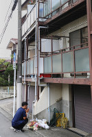 A man prays in front of a spontaneous memorial to Yua Funato, who died of suspected neglect in March this year, in front of the apartment where she lived with her parents, on June 8, 2018, in Tokyo's Meguro Ward. (Mainichi)