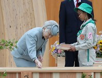 Empress Michiko sows seeds during the 69th national tree-planting festival in the city of Minamisoma, Fukushima Prefecture, on June 10, 2018. (Mainichi)