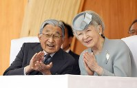 Emperor Akihito and Empress Michiko clap their hands during the 69th national tree-planting festival in the city of Minamisoma, Fukushima Prefecture, on June 10, 2018. (Pool photo)