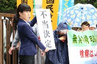 A lawyer holds a banner reading