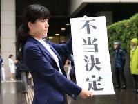 東京高裁前で「不当決定」の垂れ幕を掲げる弁護士=東京都千代田区で2018年6月11日午後1時32分、梅村直承撮影