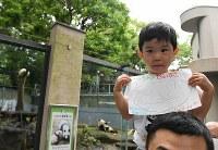 1歳の誕生日を迎えたジャイアントパンダの「シャンシャン」へのメッセージを手に観覧に訪れた男の子=東京都台東区の上野動物園で2018年6月12日午前9時43分、宮間俊樹撮影
