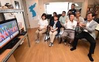米朝首脳の握手をテレビで見て拍手する在日コリアンの人たち=大阪市生野区で2018年6月12日午前10時3分、山崎一輝撮影
