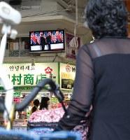 米朝首脳会談を報じるテレビニュースが流れる鶴橋商店街で足を止める人=大阪市東成区で2018年6月12日午前10時7分、小出洋平撮影