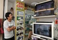 新大久保にあるリサイクルショップのテレビに映し出された米朝会談の様子を見つめる男性=東京都新宿区で2018年6月12日午前11時42分、玉城達郎撮影