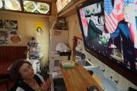 テレビで米朝会談のニュースを見る新大久保の韓国料理屋の女性。「戦争になるかもしれないより、平和のほうがいいよ」とつぶやいた=東京都新宿区で2018年6月12日午前11時40分、和田大典撮影