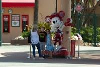 エンゼルスのロゴが入ったミッキーマウスの前で写真を撮る人々=米カリフォルニア州アナハイムで2018年6月7日、ルーベン・モナストラ撮影