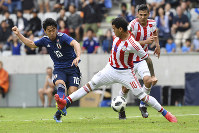 Japan's Shinji Kagawa, left, and Paraguay's William Mendieta challenge for the ball during a friendly soccer match between Japan and Paraguay at Tivoli Stadium in Innsbruck, Austria, on Tuesday, June 12, 2018. (AP Photo/Kerstin Joensson)