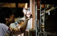 蒸留したばかりのジンの香りや色を確かめる。少しずつ蒸留されるジンと向き合う静かな時間が流れる=札幌市南区で2018年5月29日、貝塚太一撮影