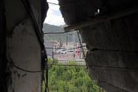 解体を前に報道陣に公開された岩手県大槌町の旧役場庁舎内部。2階の壁の亀裂からは整備の進む新しい街並みが見えた=同町で2018年6月13日午前11時42分、喜屋武真之介撮影
