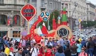 サッカーW杯ロシア大会の開幕まであと1日。モスクワのクレムリン近くの広場にあるカウントダウンボードの前では大勢の観光客が訪れ記念撮影をしていた=ロシア・モスクワで2018年6月13日、長谷川直亮撮影