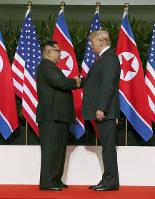 握手するトランプ米大統領(右)と北朝鮮の金正恩朝鮮労働党委員長=シンガポール・カペラホテルで12日、ロイター