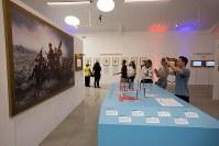「トランプ大統領ツイッター図書館」で有名絵画のパロディとしてトランプ氏やメラニア夫人らが描かれた絵(左)などを見る来館者=米カリフォルニア州ウエストハリウッドで2018年6月8日、ルーベン・モナストラ撮影