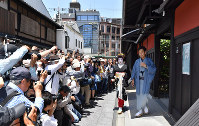 Marika goes out to meet and greet teahouse clients as many photographers take her picture in Kyoto's Higashiyama Ward on May 25, 2018. (Mainichi)