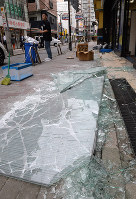 A glass window lies shattered at a store in Ibaraki, Osaka Prefecture, at 9:40 a.m. on June 18, 2018, after a powerful earthquake struck western Japan. (Mainichi)