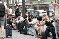 People sit on the sidewalk after train services were suspended due to the earthquake that struck the Kansai region, in Osaka's Chuo Ward on June 18, 2018. (Mainichi)