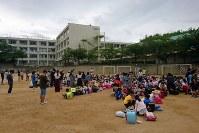 地震でグラウンドに避難した児童ら=大阪府豊中市で2018年6月18日午前8時半、小松雄介撮影