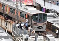 地震で緊急停止した車両から降りて歩く乗客たち=JR大阪駅付近で2018年6月18日午前9時11分、木葉健二撮影