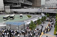 バスに並ぶ多くの人たち。後方は緊急停止したJRの車両=JR大阪駅前で2018年6月18日午前9時58分、木葉健二撮影