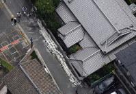 民家の外壁が崩落し、男性が下敷きになった現場=大阪市東淀川区で2018年6月18日午前10時52分、本社ヘリから小松雄介撮影