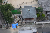 寺の建物の一部が倒壊した現場=大阪府茨木市で2018年6月18日午前11時20分、本社ヘリから小松雄介撮影
