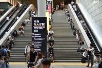 地震の影響で電車が止まり、駅の階段で座り込む人たち=大阪市中央区で2018年6月18日午前9時1分、平川義之撮影