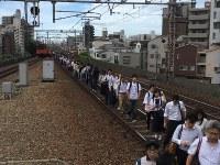 止まった電車から線路を使って移動する乗客=大阪市福島区で2018年6月18日午前9時13分、加古信志撮影