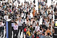 地震の情報を得ようと大型ビジョン前に集まる人たち=JR大阪駅で2018年6月18日午前9時5分、木葉健二撮影