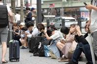 地震の影響で電車が止まり、路上に座り込む人たち=大阪市中央区で2018年6月18日午前8時53分、平川義之撮影