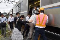 地震による緊急停止から約2時間後、車外に出る乗客ら=大阪府島本町で2018年6月18日午前9時53分