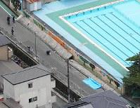 倒れた壁に女児が下敷きになった現場=大阪府高槻市の市立寿栄小で2018年6月18日午前9時58分、本社ヘリから三村政司撮影