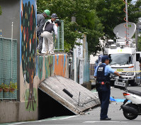 A police officer stands at the scene where a girl was trapped under a wall surrounding a pool that collapsed on top of her, in Takatsuki, Osaka Prefecture, on June 18, 2018. (Mainichi)
