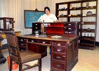 Kyushu University associate professor Misako Mishima looks over the wooden desks, shelves and other rescued items, at Kyushu University in Fukuoka, on June 1, 2018. The desk in the foreground is believed to date back to the period of the university's predecessor, Kyoto Imperial University Fukuoka Medical College. (Mainichi)
