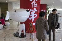 In this Nov. 11, 2017 photo, a child stands near the mascot for Chinese e-commerce giant JD.com and the words for