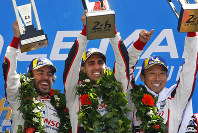 Drivers of the Toyota TS050 Hybrid No8 of the Toyota Gazoo Racing Team Sebastien Buemi of Switzerland, center, Fernando Alonso of Spain, left, and Kazuki Nakajima of Japan, right, celebrate with their trophy after winning the 86th 24-hour Le Mans endurance race, in Le Mans, western France, Sunday, June 17, 2018. (AP Photo/Thibault Camus)