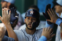 Houston Astros' Carlos Correa celebrates in the dugout after hitting a home run to tie the Kansas City Royals in the eighth inning of a baseball game at Kauffman Stadium in Kansas City, Missouri, on June 17, 2018. (AP Photo/Colin E. Braley)