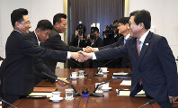 In this photo provided by the South Korea Culture And Sports Ministry, South Korean head delegate Jeon Choong-ryul, right, shakes hands with his North Korean counterpart Won Kil U during a meeting at the southern side of Panmunjom in the Demilitarized Zone, North Korea, on June 18, 2018. (South Korea Culture And Sports Ministry via AP)