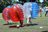 バンパーをかぶり、ぶつかり合いながらボールを奪い合う参加者たち=東京都文京区の東大弥生キャンパスで