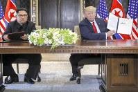 署名後、共同声明の文書を掲げるトランプ米大統領(右)と金正恩挑戦労働党委員長=シンガポール・カペラホテルで12日、AP