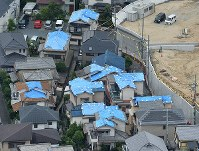 The roofs of houses are seen covered with blue tarps to prevent rain water from leaking into the structures in quake-hit Takatsuki, Osaka Prefecture, on June 19, 2018. (Mainichi)