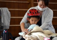 A boy, wearing a cycling helmet in case of further earthquakes, sits on his mother's lap at an evacuation center in Takatsuki, Osaka Prefecture, on June 19, 2018. (Mainichi)