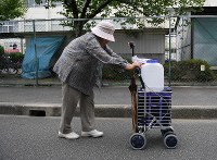 An elderly woman transports a 2-liter tank of water from an evacuation center in Takatsuki, Osaka Prefecture, on June 19, 2018. She has to visit the center multiple times to meet her needs because the amount of water provided per trip is capped at 2 liters. (Mainichi)