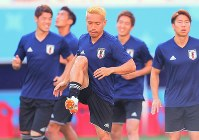 Defender Yuto Nagatomo, center, and other Japan national soccer team players warm up ahead of their 2018 soccer World Cup opener against Colombia in Saransk, Russia, on June 18, 2018. (Mainichi)
