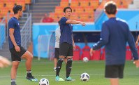 Japan national team midfielder and captain Makoto Hasebe, center, and other players warm up during a training session ahead of their 2018 soccer World Cup opener against Colombia, in Saransk, Russian, on June 18, 2018. (Mainichi)