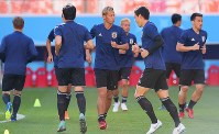 Japan national team midfielder Keisuke Honda, center, and other players warm up during a training session ahead of their 2018 soccer World Cup opener against Colombia, in Saransk, Russian, on June 18, 2018. (Mainichi)