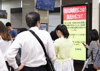 スーツや学生服姿の多くの人が電車の再開を待ち、スマートフォンなどで情報収集に追われた=JR姫路駅中央改札口前で2018年6月18日午前9時39分、幸長由子撮影