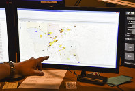 In this March 15, 2018, file photo, a supervisor shows one of the maps used by dispatchers at a 911 call center in Roswell, Ga. Apple is trying drag the U.S.'s antiquated system for handling 911 calls into the 21st century. If it lives up to Apple's promise, the iPhone's next operating system will automatically deliver quicker and more reliable information pinpointing the location of 911 calls to about 6,300 emergency response centers in the U.S. (AP Photo/Lisa Marie Pane)